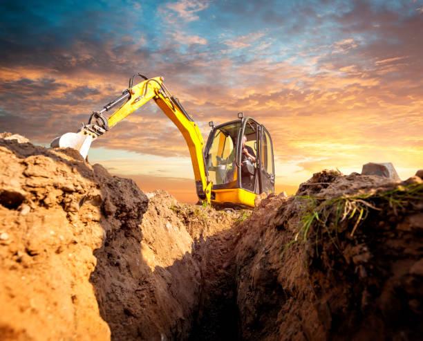 mini grävare gräver ner i bakgrunden i solnedgången - excavator bildbanksfoton och bilder