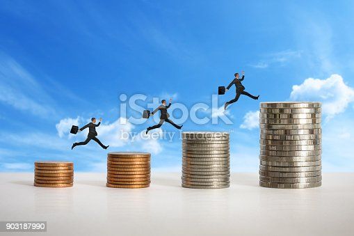 istock Mini dolls and Stacks of coins 903187990