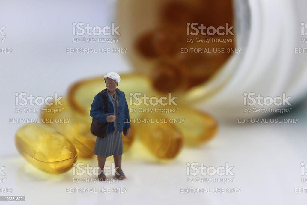 Mini figure stood by white, plastic pill bottle of vitamins stock photo