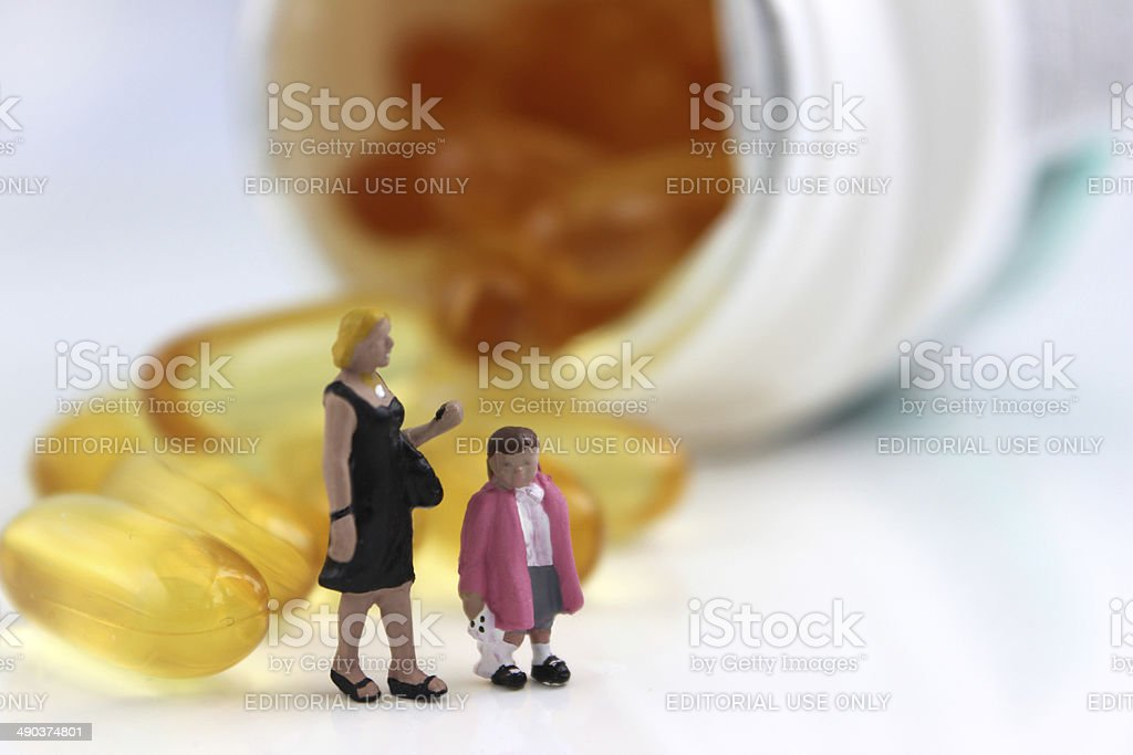 Mini figures stood by white, plastic pill bottle of vitamins stock photo