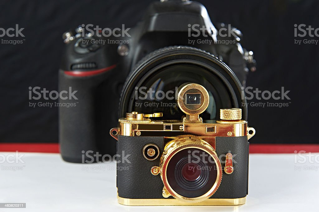 Mini gift golden camera on background of big one royalty-free stock photo