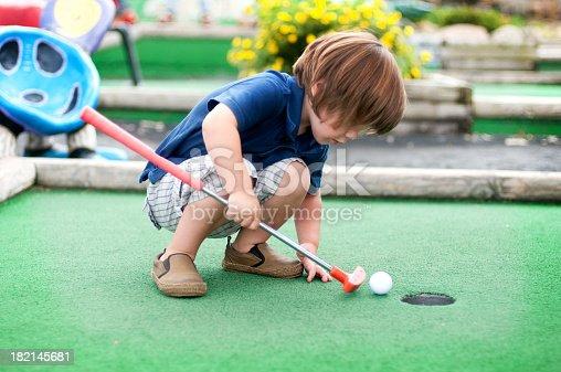 Little boy playing mini golf.