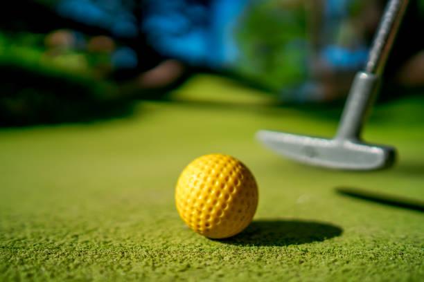 Mini Golf gelben Ball mit einem Schläger in der Nähe von Loch bei Sonnenuntergang – Foto