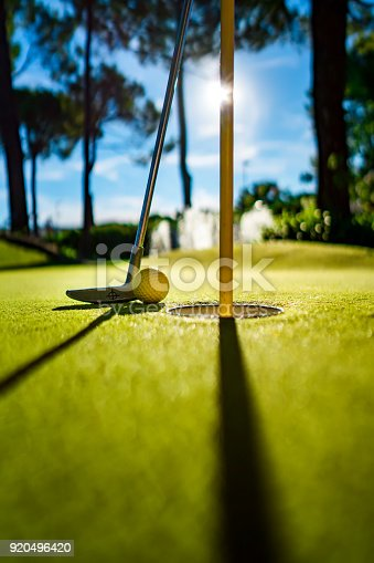 istock Mini Golf yellow ball with a bat near the hole at sunset 920496420