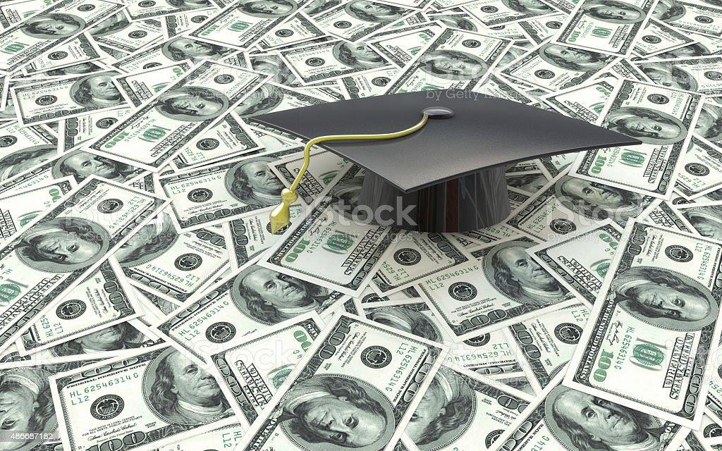 Mini graduation cap on US money -- education costs stock photo