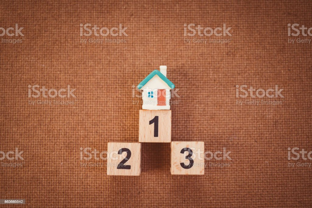 Mini house on top of wooden number stock photo