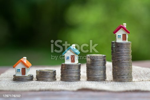 Mini house standing on a heap of coins. The concept of purchase of habitation.