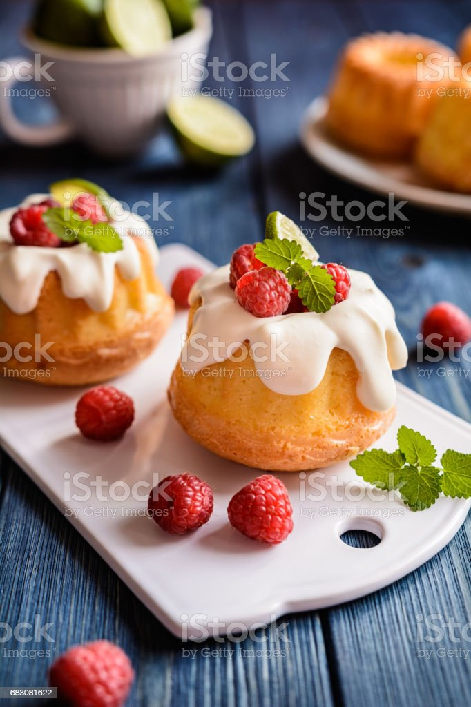 Mini lime bundt cakes with whipped cream and raspberries topping foto de stock royalty-free