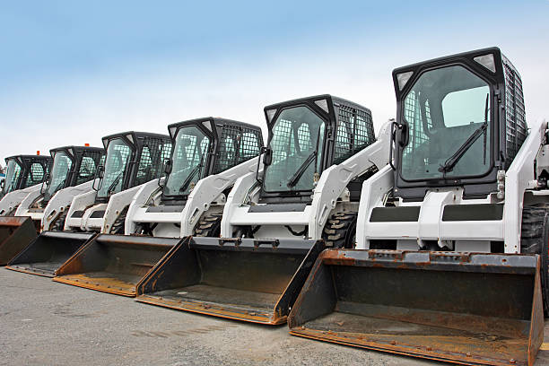 Mini Loaders In A Row Multi purpose mini loaders equipped with  scoops,  ready for snow removal in a large parking lot. medium group of objects stock pictures, royalty-free photos & images