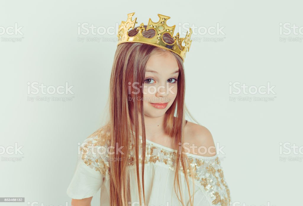 Mini Miss. Young beautiful skeptical girl wearing a crown and a white dress on Holiday looking side wards isolated white background stock photo