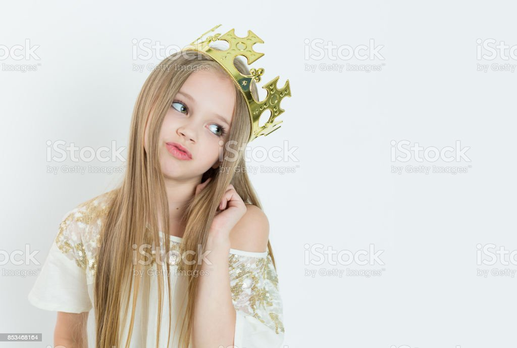 Mini Miss. Young bored girl wearing a crown and a white dress on Holiday looking side wards isolated white background stock photo