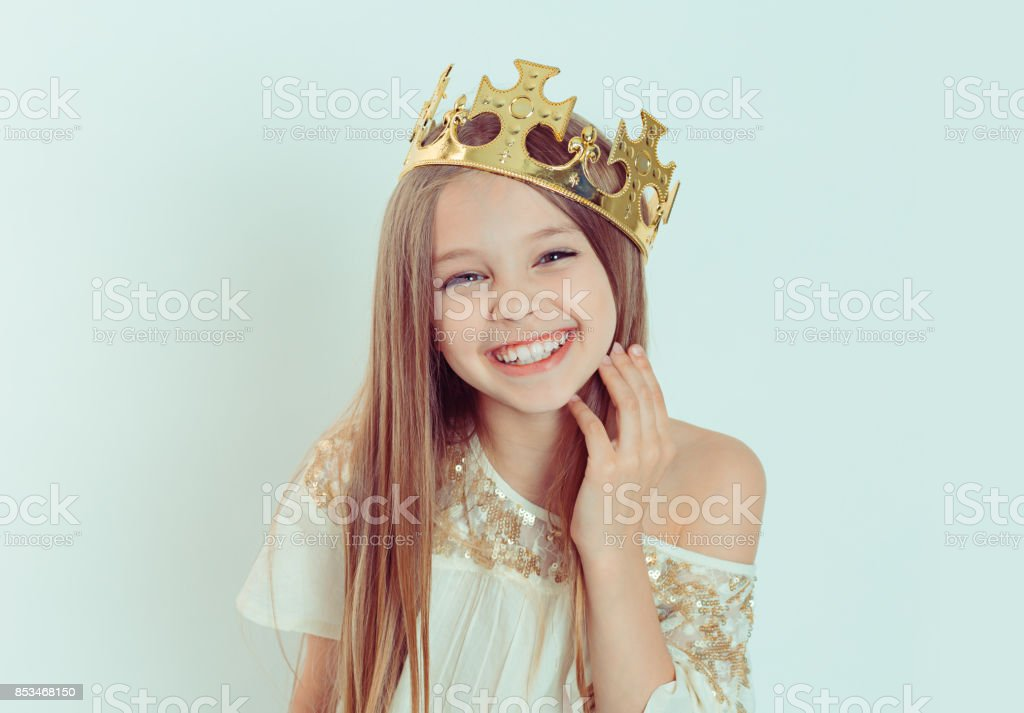Mini Miss. Young happy girl with a cute smiling laughing wearing a crown and a white dress on Holiday looking at you camera isolated green background stock photo