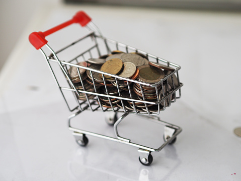 1155852718 istock photo mini model cart type in the supermarket and Many coin background out of focus background 1264242652