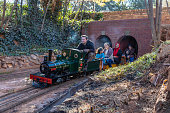 Mini model train, Sir William, travelling from a tunnel with children and parents on board at Len Rutter Park in Roodepoort, these trains are operated by the Rand Society of Model Engineers and are enthusiasts at maintaining these model trains in spotless condition to entertain children.