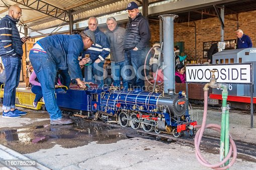 Mini model train, Wolwehoek, with enthusiasts surrounding the steam locomotive at the Woodside station in Len Rutter Park, Roodepoort, these trains are operated by the Rand Society of Model Engineers and are enthusiasts at maintaining these model trains in spotless condition to entertain children.