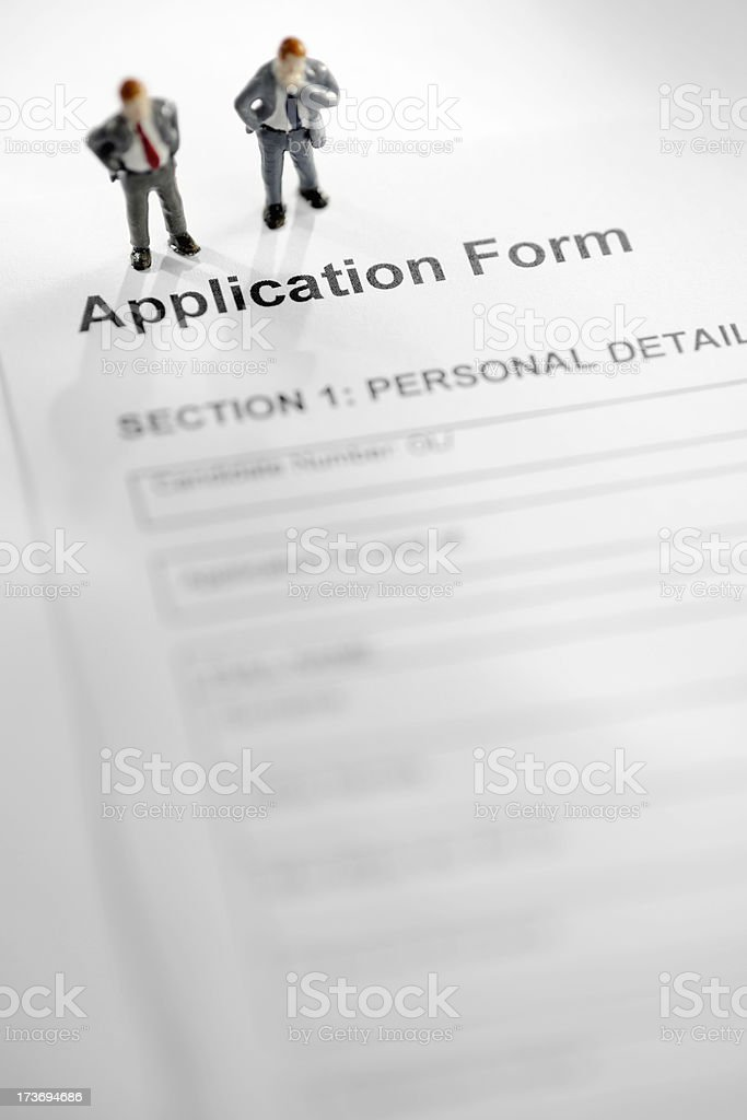 Mini Models of Businessmen on Application Form royalty-free stock photo