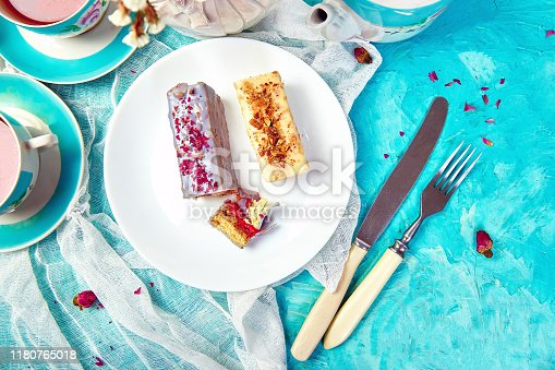 Mini Mousse Cake with chocolate, covered with blue spray and decorated with pink roses with cups of tea on blue background.