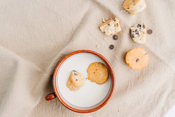 Mini muffins in a mug with milk and some muffins and chocolate chips on the background. Top view. Breakfast concept. stock photo