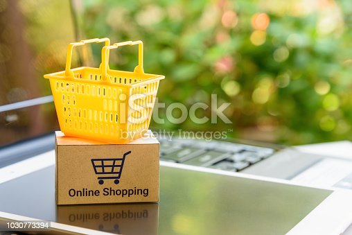 868776578 istock photo Mini orange shopping basket on a smart device and a laptop with boxes. Concept of shopping that client can buy or purchase goods or products from websites worldwide over internet by just a few clicks. 1030773394