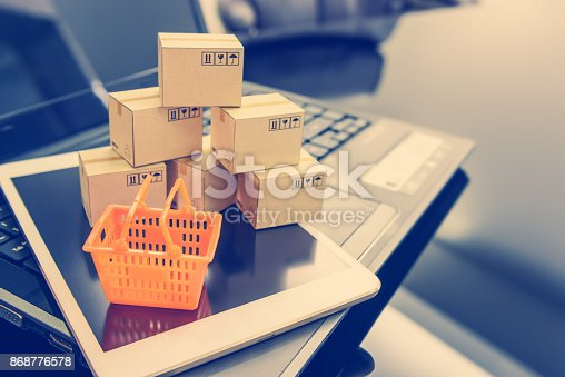 istock Mini orange shopping basket on a smart device and a laptop with boxes. Concept of shopping that client can buy or purchase goods or products from websites worldwide via internet by just a few clicks. 868776578