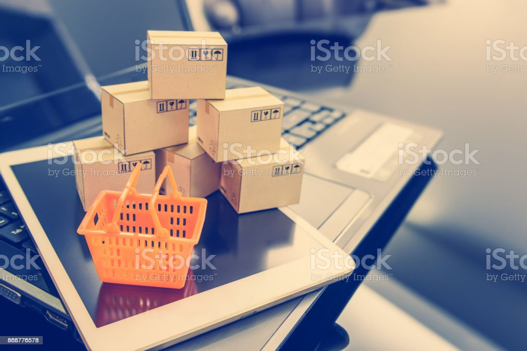 Mini orange shopping basket on a smart device and a laptop with boxes. Concept of shopping that client can buy or purchase goods or products from websites worldwide via internet by just a few clicks. stock photo