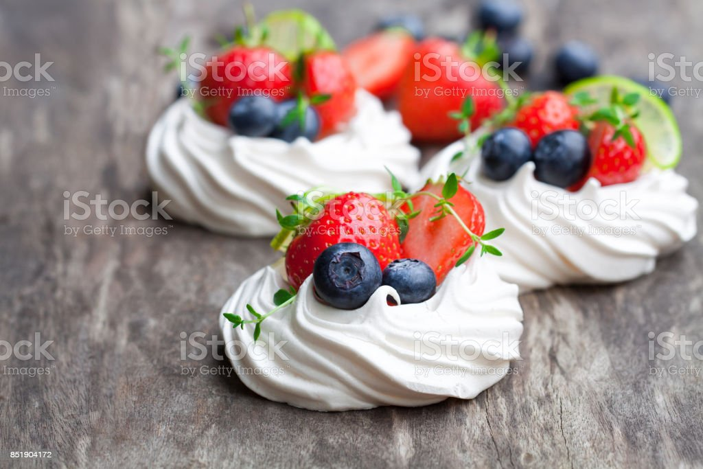 Mini  Pavlova meringue cakes with berries and lime on rustic wooden background stock photo