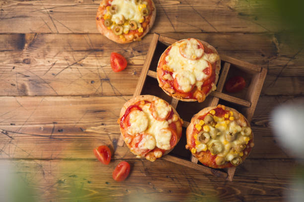 Mini pizza on wooden board. Top view from above stock photo