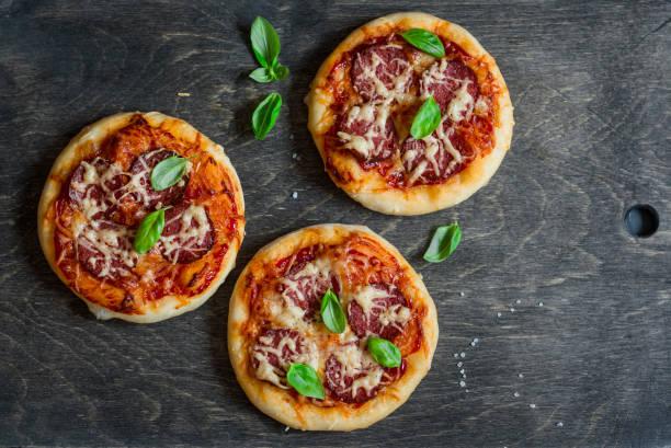 mini salami pizza on a dark wooden background, top view - fladenbrotpizza stock-fotos und bilder