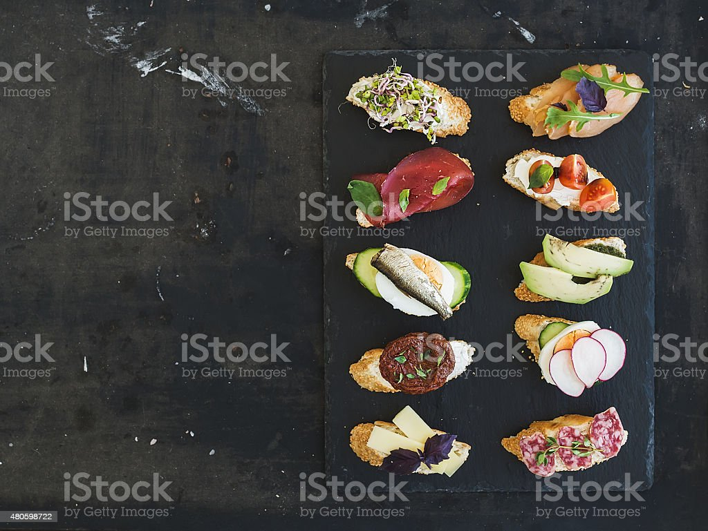 Mini sandwich set. Variety of small sandwiches on black backdrop stock photo