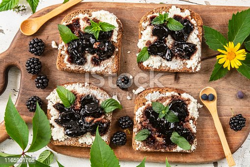 Mini sandwiches with black bread, cottage cheese and jam of berries on rustic cutting board on a white wooden table.  Delicious snack, appetizer, antipasti. Gourmet
