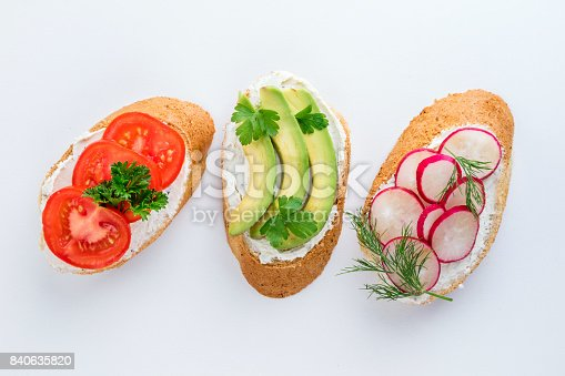 istock Mini sandwiches with cream cheese, vegetables and avocado. Variety of sandwiches on white background, top view 840635820