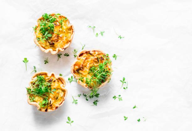 mini tarte salée avec du poulet, poireau, fromage sur fond clair, vue de dessus. délicieux apéritif, snack, petit déjeuner, tapas - quiche photos et images de collection