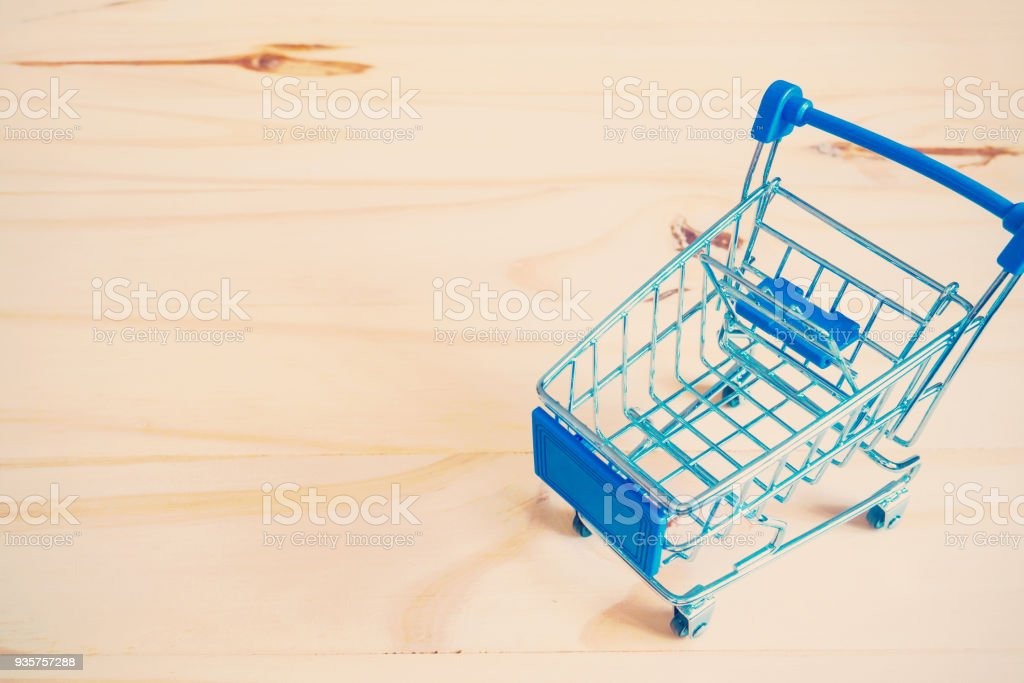 Mini shopping cart on wooden background stock photo