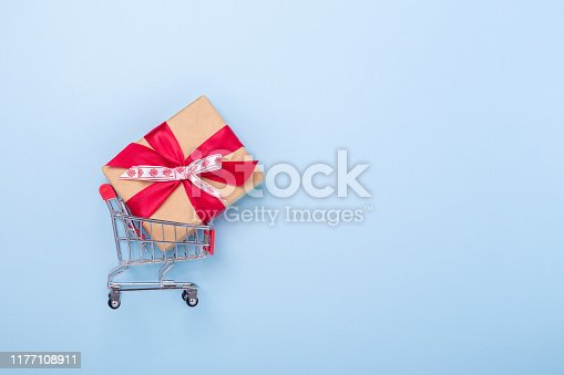 Mini shopping carts and gift box on blue background Concept of Christmas sale Top view Copy space - Image