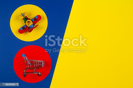 Mini shopping trolley cart and small toy airplane on red yellow navy blue background. Toys, kids, online shopping, buy, sale, discount concept.