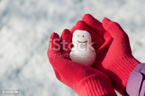 istock Mini snowman in girl hands with red wool gloves. 510406786