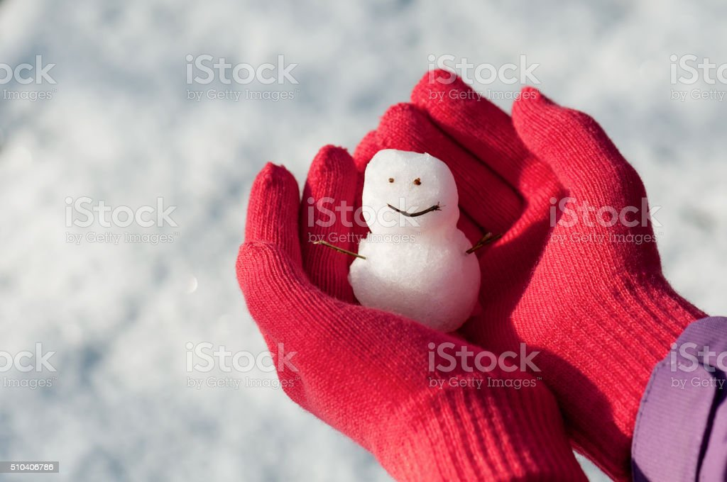 Mini snowman in girl hands with red wool gloves. stock photo