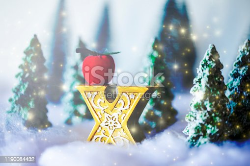 istock Mini snowy Christmas trees in the forest. Bokeh lights background 1190084432