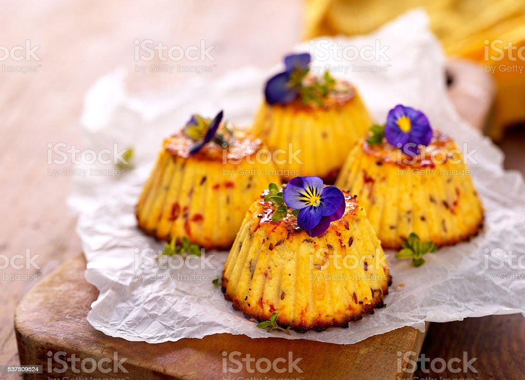 Mini spicy cheese cake with edible flowers stock photo
