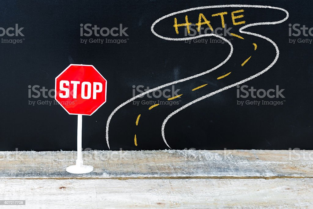 Mini STOP sign on the road to HATE stock photo