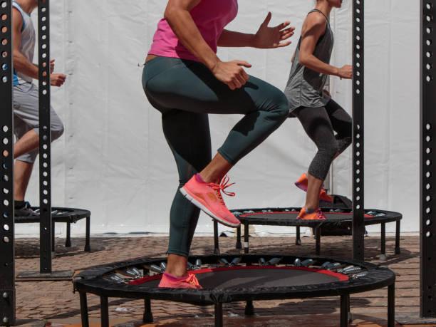mini trampolín entrenamiento: chica haciendo ejercicios de fitness de clase en el gimnasio - trampolín artículos deportivos fotografías e imágenes de stock