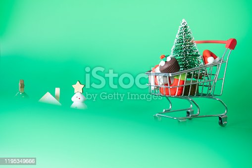 511190632 istock photo Mini trolley cart with ornaments in Christmas on green background. Concept of Christmas sale 1195349666