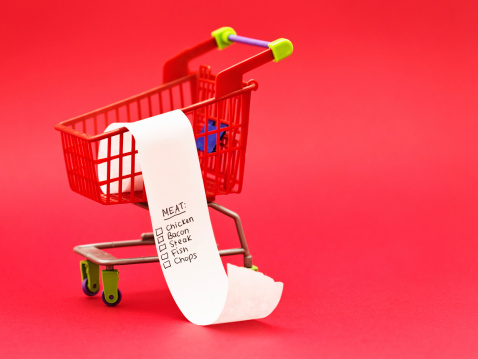 A miniature supermarket trolley contains a list headed Meat,  maybe for a protein-loving man?