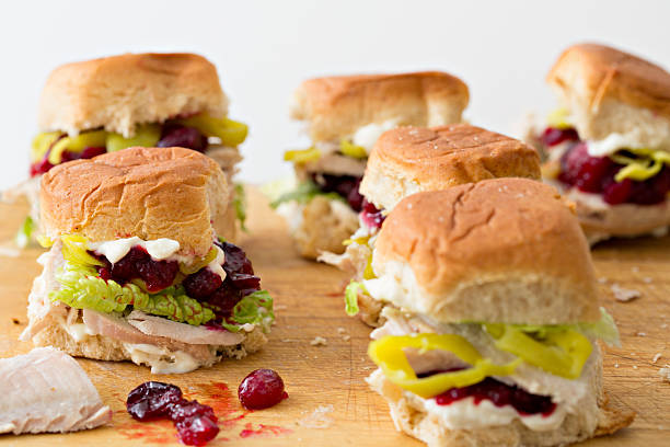 Mini Turkey Sandwiches A close up horizontal shot of several miniature turkey sandwiches made from sliced leftover thanksgiving turkey, cranberry sauce, mayonnaise, lettuce, deli sliced pepperoncinis and sweet Hawaiian honey wheat rolls. The white background provides some copy space on the top of the picture leftovers stock pictures, royalty-free photos & images
