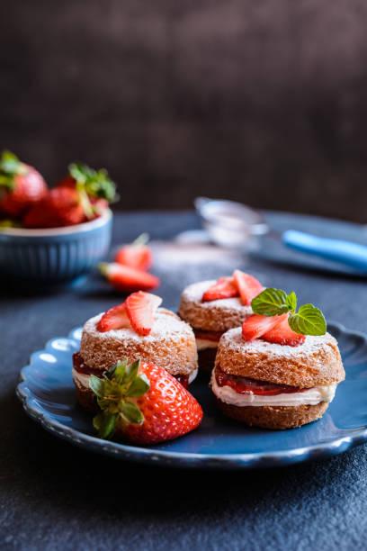 mini victoria sponge cakes with whipped cream and strawberries - hausgemachte zuckerplätzchen stock-fotos und bilder