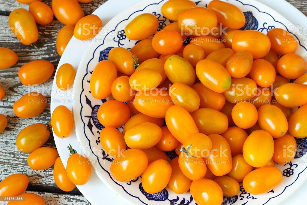 Mini yellow cherry tomatoe in white dish stock photo