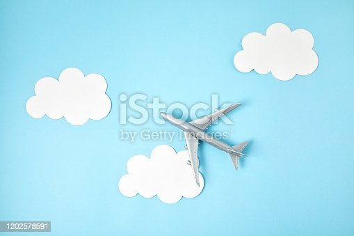 624266324 istock photo Miniature airplane over blue background with paper clouds. Travel tourism, airlines, low cost flights concept. Top view, flat lay. 1202578591