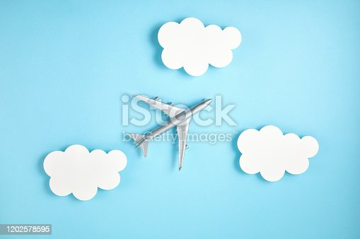 624266324 istock photo Miniature airplane over blue background with paper clouds. Travel tourism, airlines, low cost flights concept. Top view, flat lay. 1202578595