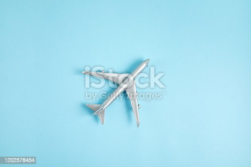 624266324 istock photo Miniature airplane. Travel tourism, airlines, low cost flights concept. Top view, flat lay. 1202578454
