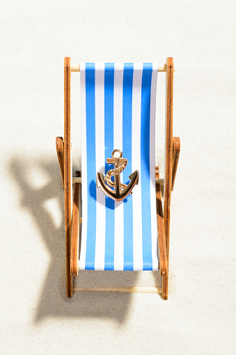 istock Miniature anchor on a striped chaise longue 937975920